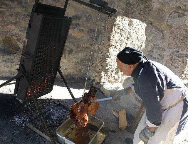 Hombre asando lacón en el mercado de Navidad del Castillo de Chillon