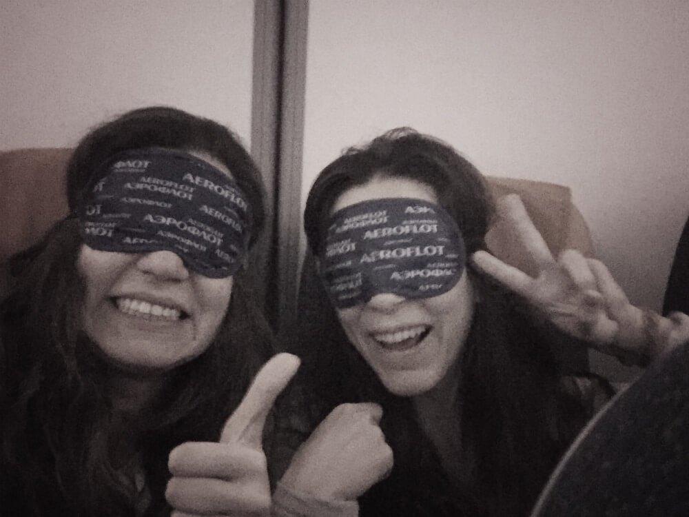 Claudia y Lucía preparadas para dormir cada una en su postura favorita en avión