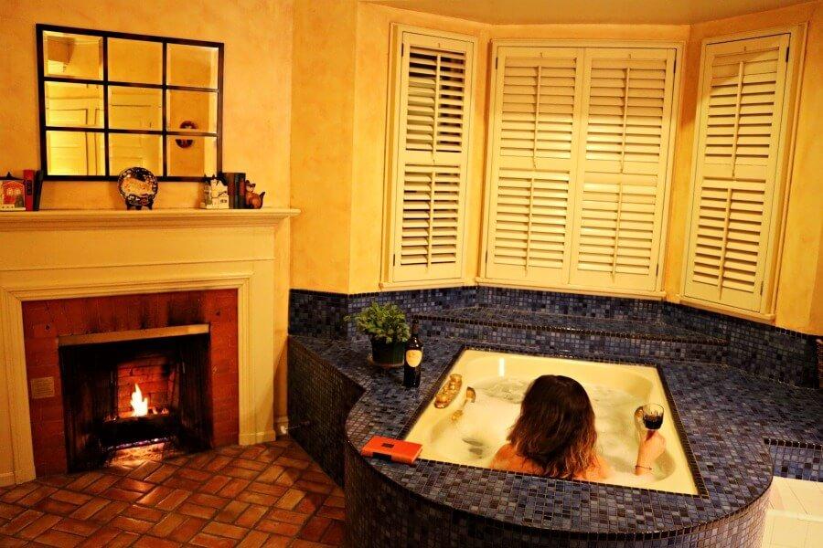 Chimenea y bañera en la habitación Eberle de Cheshire Cat Inn