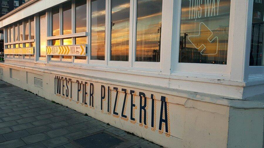 Atardecer reflejado en la West Pier Pizzeria de Brighton
