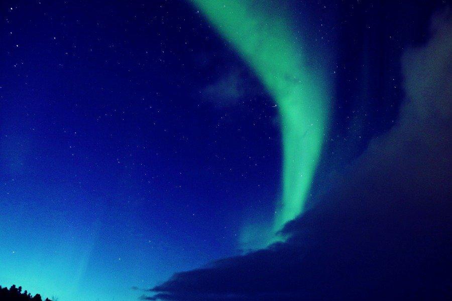 Aurora boreal entre nubes en Noruega Ártica