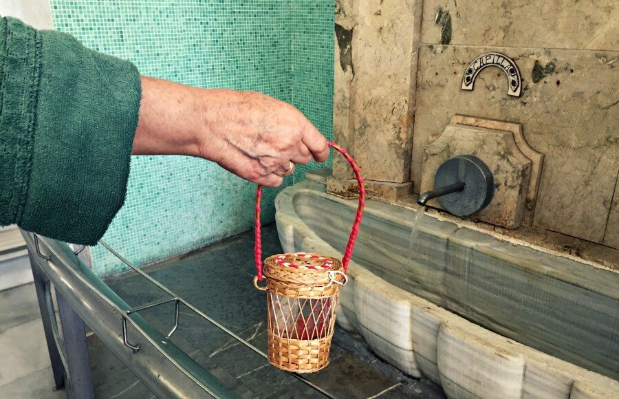 Señora llenando su cantimplora de agua de Lanjarón