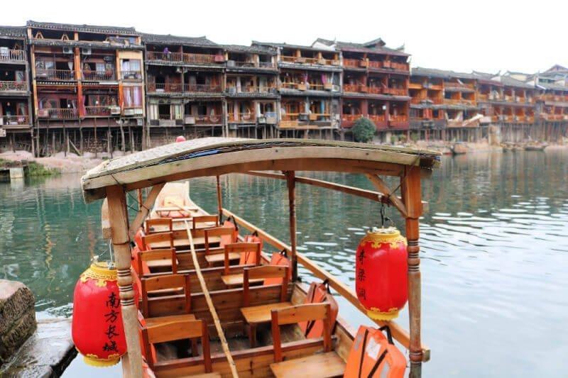 Casas sobre pilotes y barco de bambú en Fenghuang
