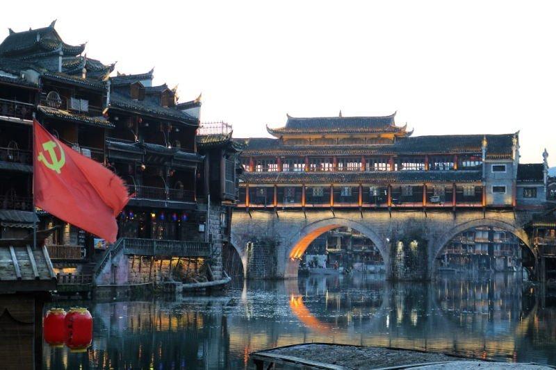 Puente de Fenghuang y bandera hoz y martillo en China