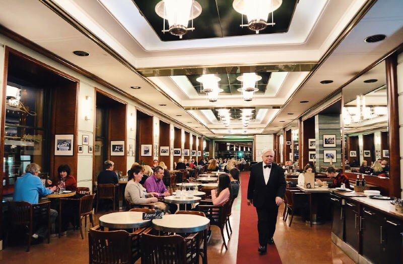 Ambiente cosmopolita en el Café Slavia de PragaLa cafetería más sofisticada de Praga - Cafeterías más bonitas de Praga