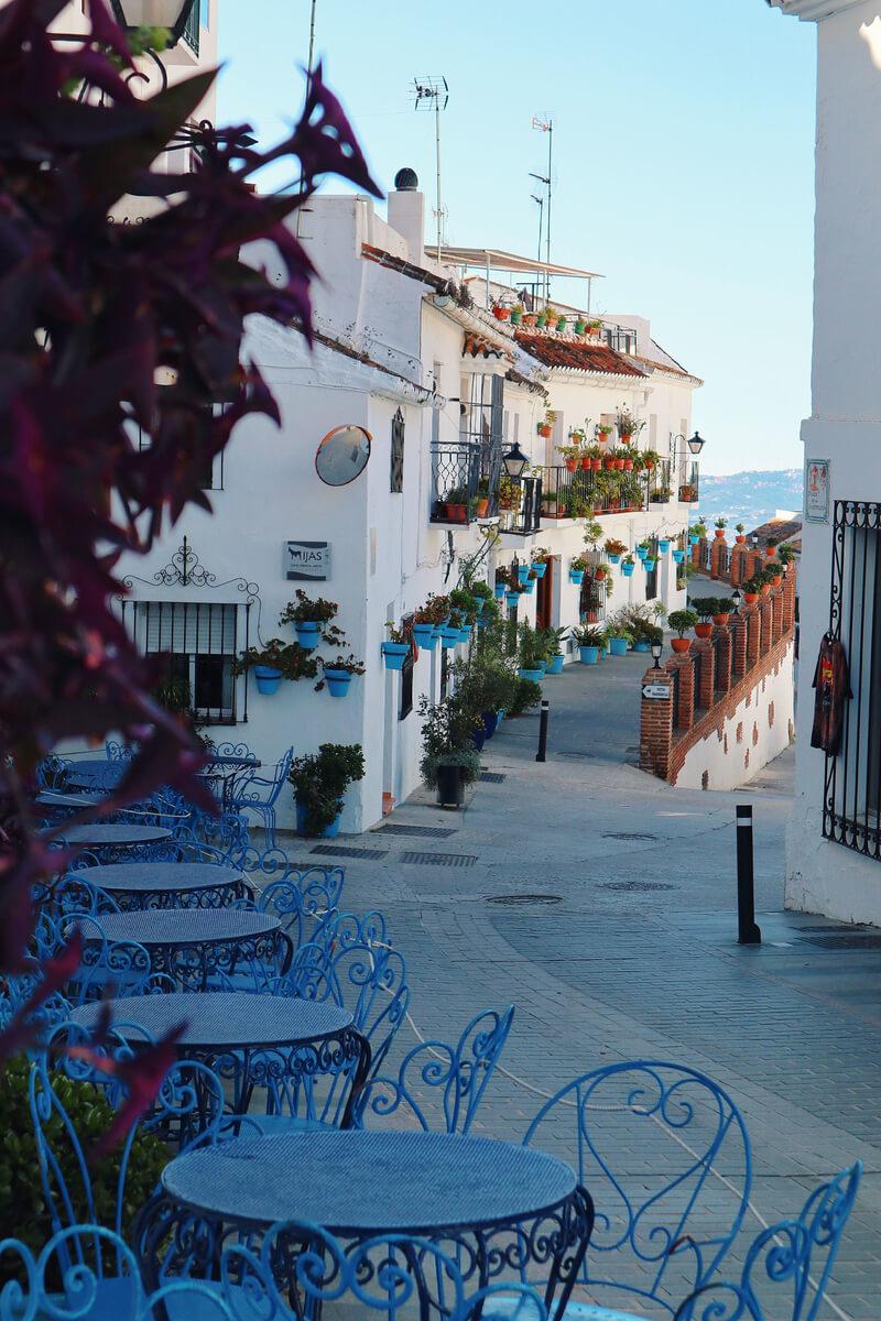 Calles llenas de flores y macetas azules